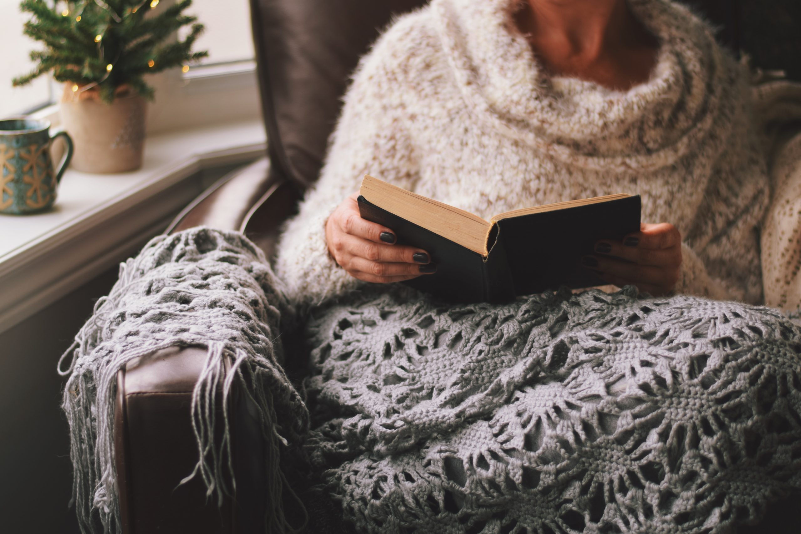 Girl cuddled up with a book reading for a hygge experience.