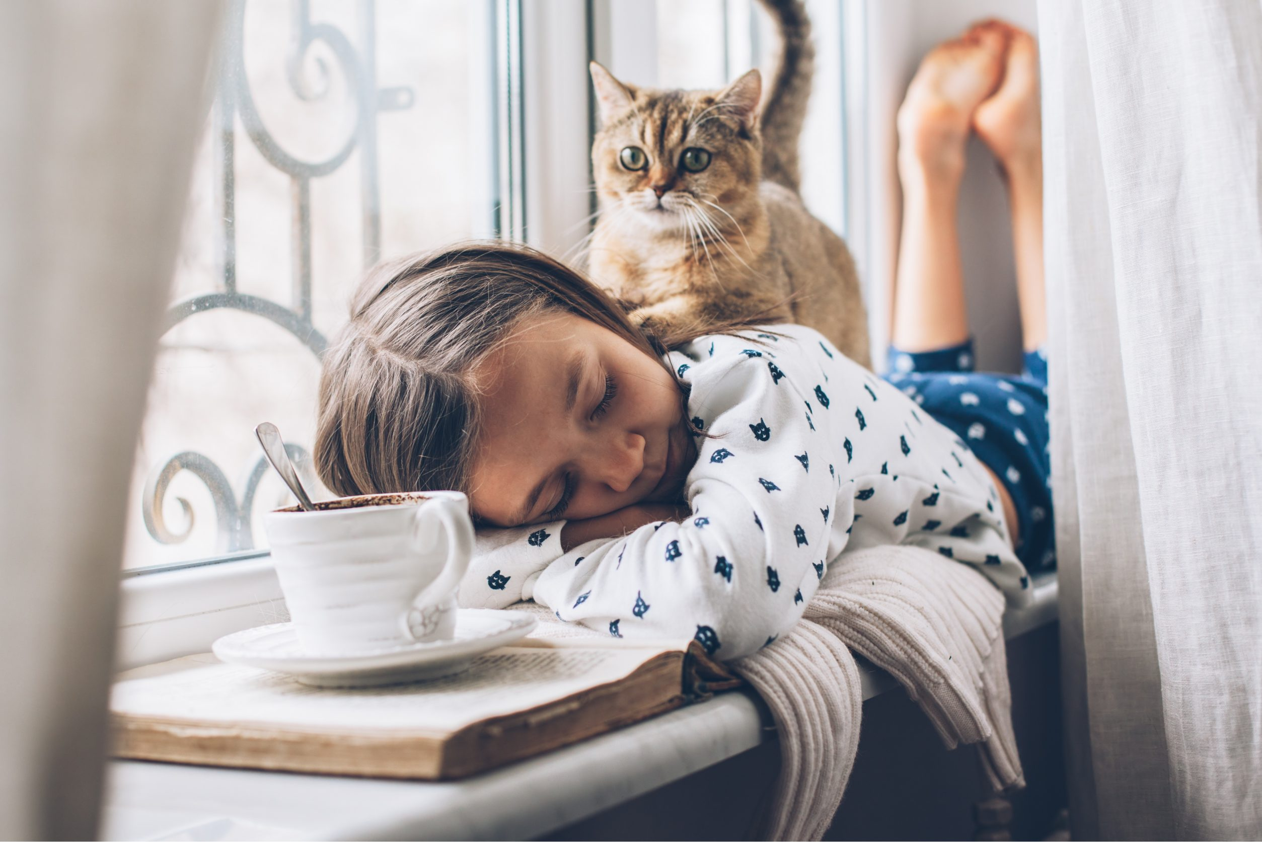 Little girl and cat cuddling making a hygge experience.