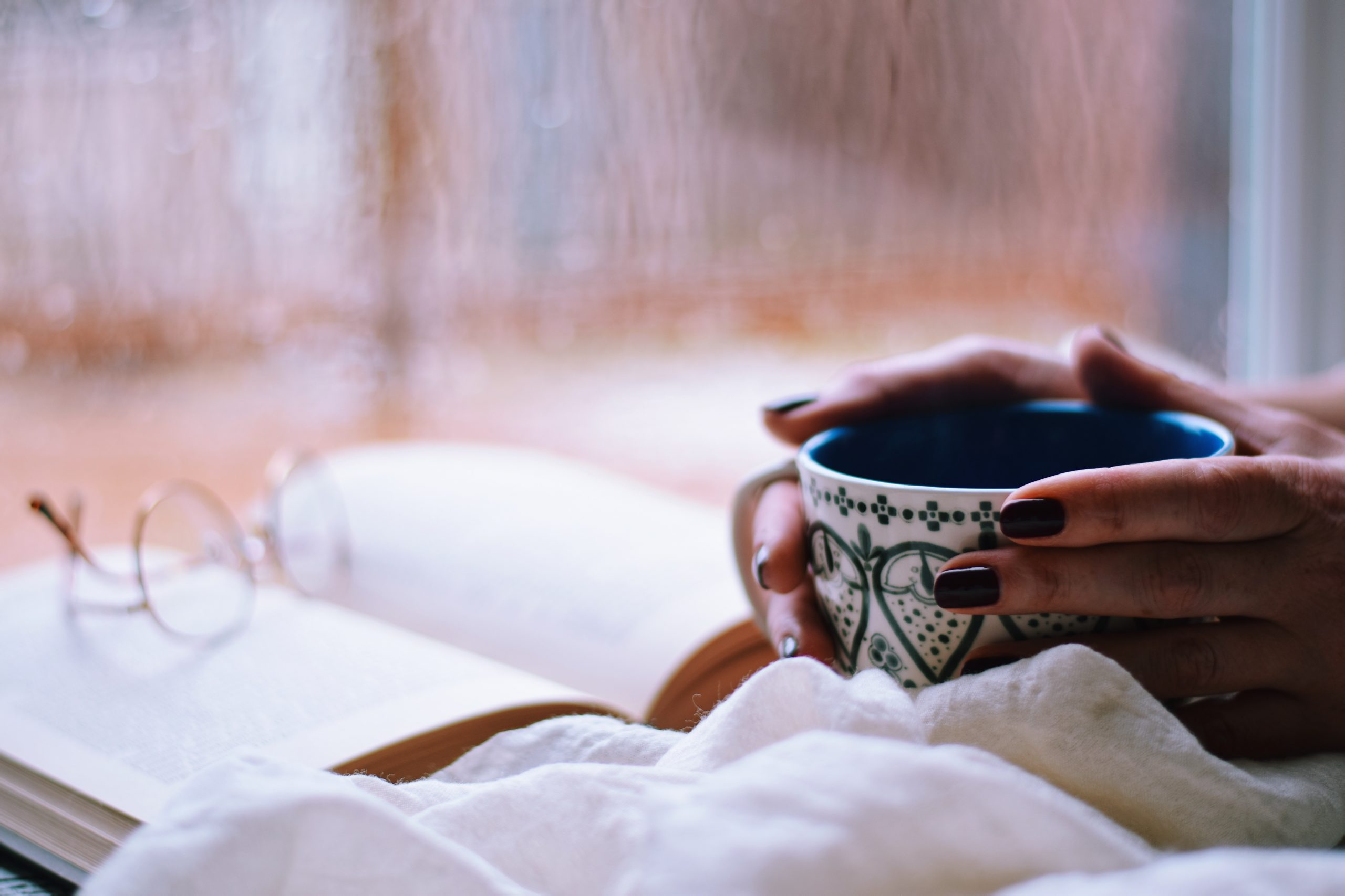 Girl cuddled up with a hot cup of cocoa and a book.